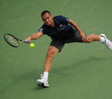 CINCINNATI, OH - AUGUST 12:  Mikhail Youzhny of Russia returns to Jo-Wilfried Tsonga of France during a match on day 4 of the Western & Southern Open on August 12, 2014 in Cincinnati, Ohio.  (Photo by Jonathan Moore/Getty Images)
